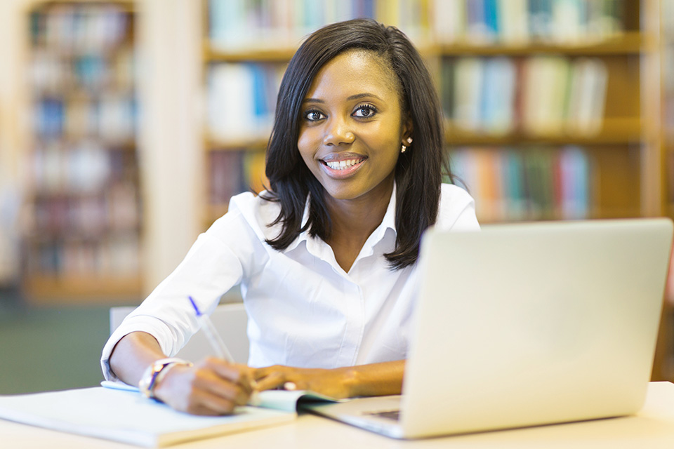 Woman smiling while writing on notebook