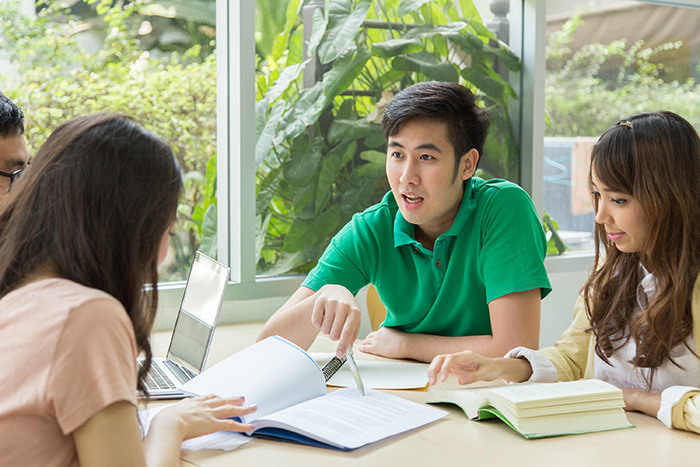 Man teaching three other students